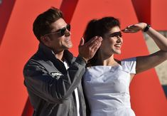 Zac Efron Alexandra Daddario Photos - US actors and stars of the new movie Baywatch, Zac Efron (L) and Alexandra Daddario (R) wave to fans at a promotion for the movie on Bondi Beach in Sydney on May 17, 2017..The new Baywatch movie opens in cinemas on June 1, 2017. / AFP PHOTO / PETER PARKS - 'Baywatch' Photo Call