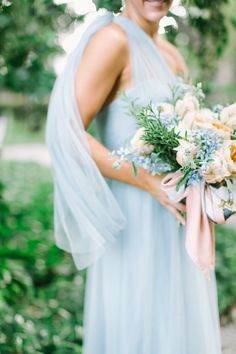 Side view of soft pale blue bridesmaids gown that ties in a variety of ways. This bridesmaids dress is tied at the shoulder. Beautiful and lush bridesmaid bouquet with pastel pinks and blues and pops of greenery and tied with a vintage hermes scarf.  Flowers by Ashlye McCormick Designs, Wedding Planning by Bella Baxter Events, As Seen in Southern Bride Magazine, Photo by Weddings by Christopher & Nancy