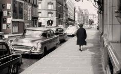 Paris 1962, une dame passe devant l'Hôtel Bristol, rue du Faubourg-Saint-Honoré. Autre époque, autres voitures. On voit une belle 1954 Buick Special. Une Américaine à Paris.