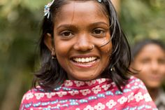 An Indian girl laughs after getting a drink from her village's charity: water pond sand filter.