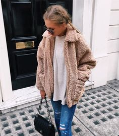 Cozy blush shearling jacket over white top with blue jeans.