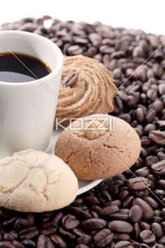 flavorful cookies with a dark coffee - A flavorful cookie with a dark coffee on a white plate surrounded by coffee beans