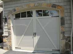 Coachman Collection insulated steel and composite carriage style garage doors, Design 22 with ARCH windows in desert tan with almond overlays. www.clopaydoor.com. By Otero Signature Homes via Houzz.