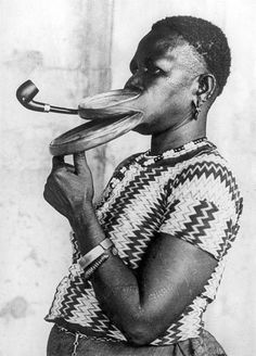 Madam Gustika of the Duckbil tribe smoking a pipe with an extended mouthpiece for her large lips during a show in a circus. United States, New York, 12 April 1930