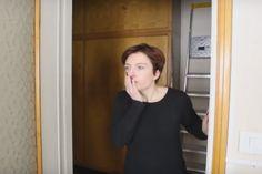Donna guarda perplessa dalluscio di casa