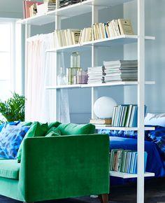 3 ELVARLI Elemente in Weiß zwischen einem grünen Sofa und dem Schlafbereich als Raumteiler positioniert.