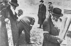 Cracow, Poland, Scorched books and Torah scrolls being collected by elderly Jews in a burnt-out synagogue in the ghetto.