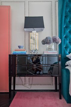 black lacquered bedside table, teal tufted headboard, gray walls with nailhead design
