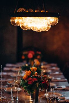Welcoming vintage evening dinner party creative setting with wood table & chairs in a cozy moody dining room. Candlelit with pink & orange flower centerpieces.