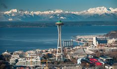 Aerial Photography by Jay Dotson.  Seattle Space Needle on Blue Friday in Seattle, flying the Seattle Seahawks 12th man flag with the Olympic Mountains in the background.