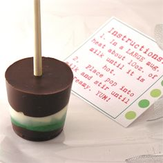 Hot Chocolate Pops (in a variety of flavors and colors) hardened over a marshmallow on a stick. You stir them into hot milk and make the most creamy, delicious hot chocolate ever. The best part? You can make them WAY ahead. Free printable directions. Great little diy gift idea for Christmas.