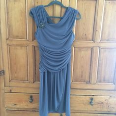 Scarlett Nite Cocktail Dress in Gunmetal Grey Scarlett Nite cocktail dress with matching brooch. Polyester spandex blend. Figure flattering shirring across the bust and waist. Faux wrap fully lined skirt. Size 12 runs small fits more like a 10. Never worn with tags. Scarlett Nite Dresses