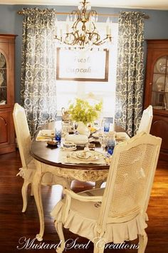 love the warm-toned wood & off-white chairs. this is almost my exact dining room set up - down to the two corner hutches... :D This might just work!
