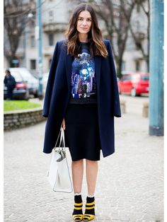 Leila Yavari wearing a navy knee-length coat thrown over a graphic tee and black skirt with yellow heels and socks underneath