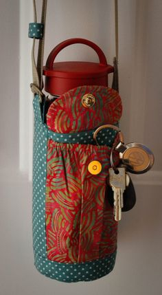 Insulated water bottle/coffee mug sling - fits large bottles. 7 deep, 3.5 diameter Walk hands free. Convenient for those who walk pets, kids or have carpal tunnel or Arthritis. Perfect for accessory for vacationing. Made of quality quilter cotton, 2 elastic pockets to fit your keys and phone, adjustable strap. Teal/Red batik. Probably stating the obvious, but listing is for sling only. Bottle, keys, or door, not included :)