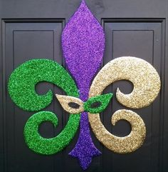 Or how about this clever twist on a fleur de lis door hanger? All you need is a slightly altered fleur de lis stencil and glitter! Mardi Gras Wreath, Mardi Gras Decorations, Mardi Gras Beads, Candle Decorations, Mardi Gras Centerpieces, Mardi Gras Carnival, Mardi Gras Party, New Orleans Mardi Gras, Masquerade Party