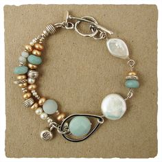 "The fun bracelet is the perfect companion to a weekend at the shore.  Hand picked white and tan pearls are set among deep amazonite and shimmering silver making for a truly individual piece.  7 1/2"" L. with a toggle closure"