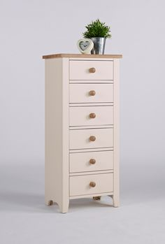 New England Painted Tower Chest Of Drawers This is a beautiful chest of drawers Clean fresh lines and lightly painted in ivory  It has six deep drawers The drawers are tongue and groove With contrasting wooden knob handles The top is solid ash that has been lightly lacquered This is a satin finish which is resilient and serves to protect the natural beauty of the ash The frames are solid pine With high quality MDF panelling Finished in a knock resistant paint in ivory