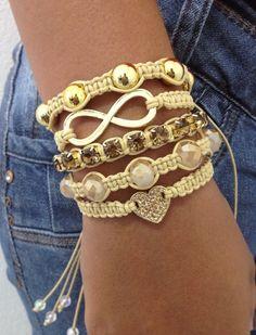 Kit de 5 pulseiras confeccionadas em macramé na cor bege, sendo:  - 1 pulseira com coração dourado e strass topaz  - 1 pulseira de corrente de strass topaz  - 1 pulseira de perolas douradas  - 1 pulseira de cristais facetados bege  - 1 pulseira com símbolo do infinito    > Pulseiras ajustáveis, n...