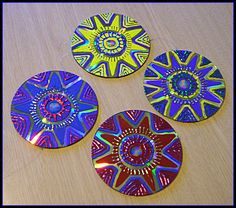 Cds are glued , back to back and strung together with fish line . They are painted with acrylics , and metallic leaf .