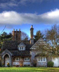 """""""Double Cottage,""""  one of the larger storybook cottage designs at Blaise Hamlet.       It is constructed of random rubble stone with magnificent brick chimney stacks and a stone tile cross-gabled   roof."""
