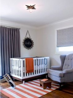 gray and orange nursery. Love the rug and gray chair