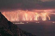 Setenta Rayos, fuego en el cielo  Para realizar esta fotografía el Chris Kotsiopoulos disparó su cámara 90 veces durante 83 minutos.  Descartó 20 exposiciones para evitar la saturación lumínica de la foto.  Una imagen que da una idea de la enorme cantidad de energía eléctrica que descarga una tormenta.  La fotografía ha sido tomada en la isla de Ikaria (Grecia).