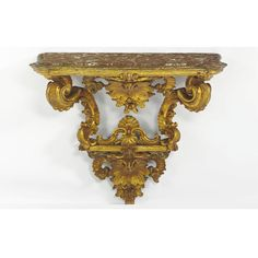 An Italian Rococo carved giltwood console with an inset red mable top above a beveled apron centered by a stylised scallop-shaped cartouche with flowers flanked by S and C-scroll supports on a similarly carved scallop cartouche; incorporating 18th century elements.
