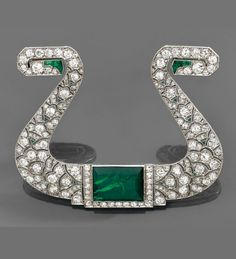 An emerald, diamond and platinum brooch, circa 1920.  Designed as a stylised 'lyre', pierced and set with brilliant-cut diamonds and calibré emeralds, centring a rectangular emerald cabochon. #ArtDeco #brooch