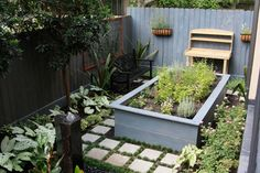 Secluded Bellaire Garden Landscape by Nature's Realm in Houston, Texas - Small manicured garden with pavers, raised herb / vegetable garden, seating, potting bench, and fountain.
