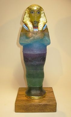 "Judi Charlson Hatshepsut (the woman who would be king)   kiln cast glass, gold, silver, paint, steel, wood base  19"" x 7.5"" x 6.5"""
