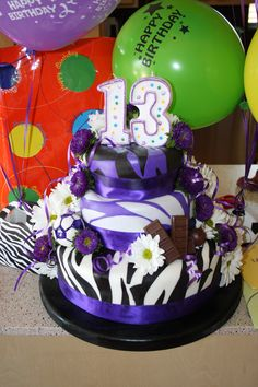 Birthday cake for my 13th year old daughter...full of red velvet, chocolate and white cake, covered with different colored zebra pattern fondant, chocolate bar, Hershey's Bar, streamers, fresh flowers and a purple/wht soccerball.