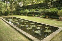 """Russel Page war berühmt für seine """"Neo-Renaissance-Gärten"""". Sie sind in ihrer grafischen Wirkung noch immer atemberaubend - aber auch atemberaubend teuer in Anlage und Unterhalt! Trotzdem, wie die Schwimmpflanzen-Tuffs die Anordnung der Buchs-Kugeln im Hintergrund aufnehmen, ist große Gartenkunst! Sie scheinen sich im Wasser zu spiegeln, obwohl das gar nicht möglich ist."""