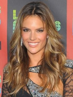 Iridescent golden highlights lift and add life to Alessandra Ambrosio base color. Her long layered locks appear more shiny and dimensional with golden highlights streaked through the lengths.