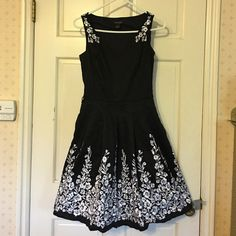 White House Black Market Fit Flare Floral Dress 0 Beautiful v-neck White House Black Market cotton dress, size 0. It's fit and flare style, with a full, pleated skirt that has a black lining underneath and pockets (love that!). There are white embroidered flowers on the straps and hem of the skirt. It also has belt loops at the waist, but no belt is included. Gorgeous dress!  Dry clean. White House Black Market Dresses