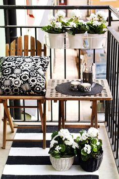 Tiny balcony..love the black and white design. Hanging planters to the inside is a nice feature as well