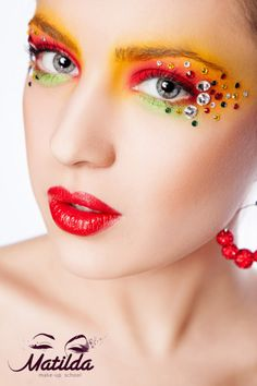 Vibrant yellow, green and green eye makeup with multi-color rhinestone accents. Matilda Make-up School.