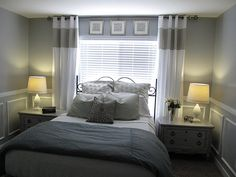 Bed in front of window with bedside tables on each side. ...I also like the frames.