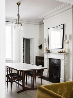 a well curated dining room with modern touches and a fireplace in this historic home   house tour on coco kelley