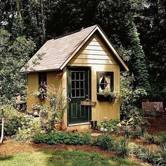 English Cottage Garden Shed. Colors are interesting. The door is the same color as the trim. Dark Green door and trim. Yellow siding. #englishgardens