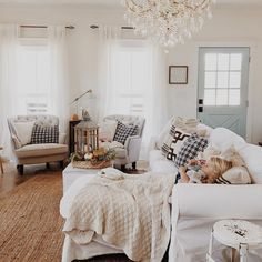 Cozy living room with a gorgeous chandelier. Loving the front door as well.
