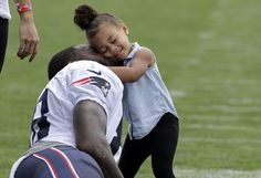 New England Patriots tight end Martellus Bennett cuddles with his daughter, Jett, after NFL football training camp, on August 16, 2016, in Foxborough, Massachusetts.