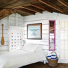 Nautical cottage bedroom with curtains that have a signal flag design. CoastalLiving.com.