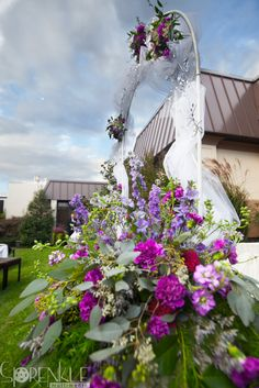 Purple and white flower arrangement by buteratheflorist.com outdoor wedding altar at Eden Resort in Lancaster, PA.