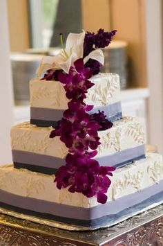 Square three tier wedding cake with cascading flowers