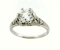 """This breathtaking """"Tiffany & Co"""" platinum and diamond engagement ring has been excellently preserved. The crown jewel of this ring is a 1.65ct old european cut diamond (G - VS1) held securely in place by six prongs. The head and shoulders of the ring are adorned in filigree work and mil-graining accented with eighteen additional single cut diamonds."""