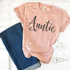 """Every auntie needs this super cute and comfy auntie shirt! This cute and incredibly soft auntie shirt makes the perfect pregnancy announcement shirt. Featuring the word """"Auntie,"""" this beautiful aunt shirt has been expertly designed to not rub off, fade, or peel and comes in three"""