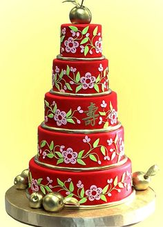 This huge Chinese red five tier wedding cake was made for an Asian theme wedding and has a Chinese symbol set in the colour gold. Accents of pastel pink and light green. At the bottom of each tier is a striking thick gold piping of fondant uplifting and complimenting the red. The final touch is a life size gold apple wedding cake topper. From www.justfab.com