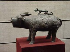 """Ox-shaped Zun, Western Zhou dynasty.  Shaanxi History Museum, Xi'an.   This zun wine container is cast in the shape of an ox with crescent-shaped, laid-back horns. The liquid is poured out of its mouth. The vessel's square lid is fitted with a tiger handle, and an abstract design covers its body. The ox's tail forms the handle of the vessel. At 15"""" long, the vessel is a rather large example of its type."""