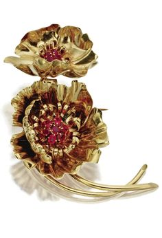 18 KARAT GOLD AND RUBY FLOWER BROOCH, VAN CLEEF & ARPELS, PARIS, CIRCA 1945 Designed as two poppies of polished gold, their centers clustered with round rubies, signed Van Cleef & Arpels, Depose 50146, French assay marks.